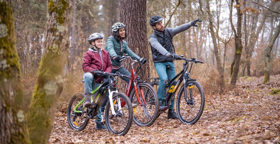 trois personnes dans la foret faisant du vélo