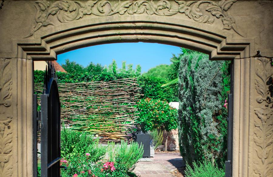 Vu des jardins au travers d'une porte en pierre