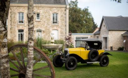 Une voiture ancienne jaune devant le relais de Fleurette