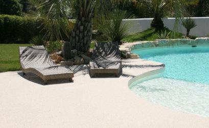 Une plage de piscine en granit couleur sable avec des transats