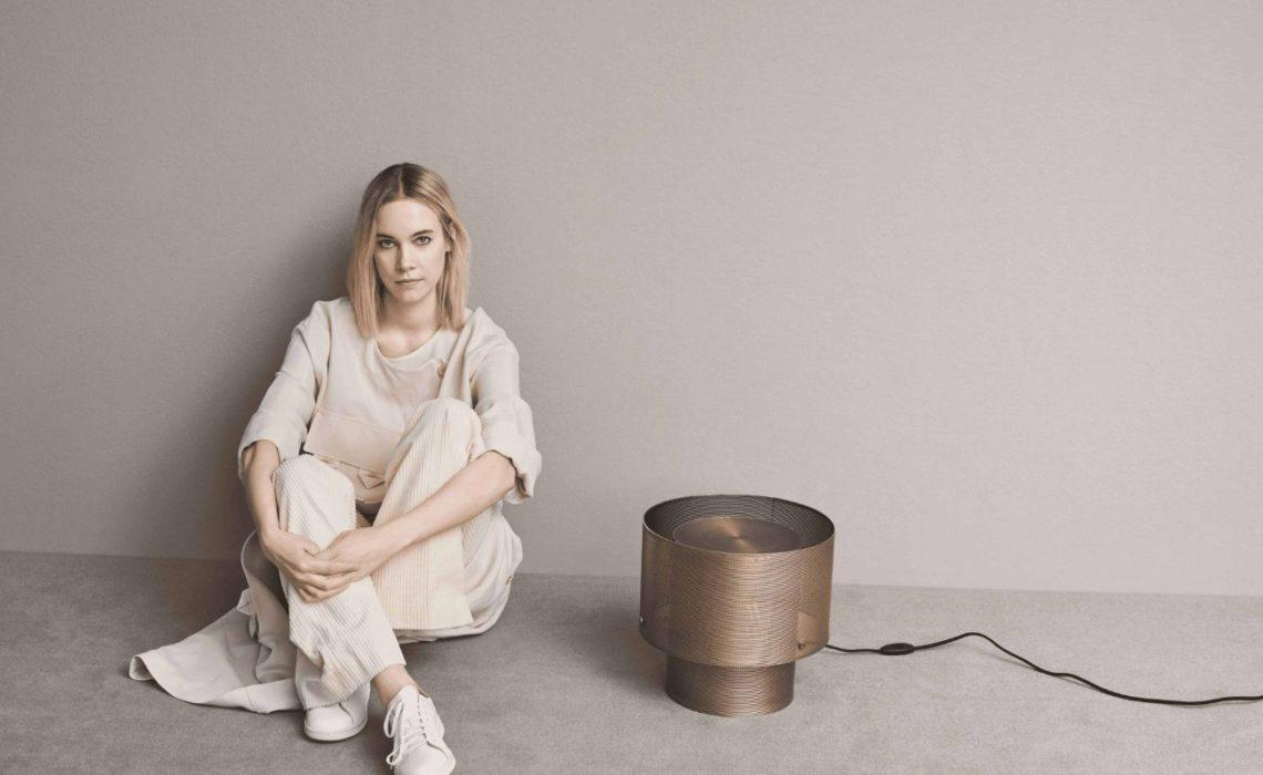 Photo portrait de la designer Meike Harde assise par terre à coté d'un luminaire