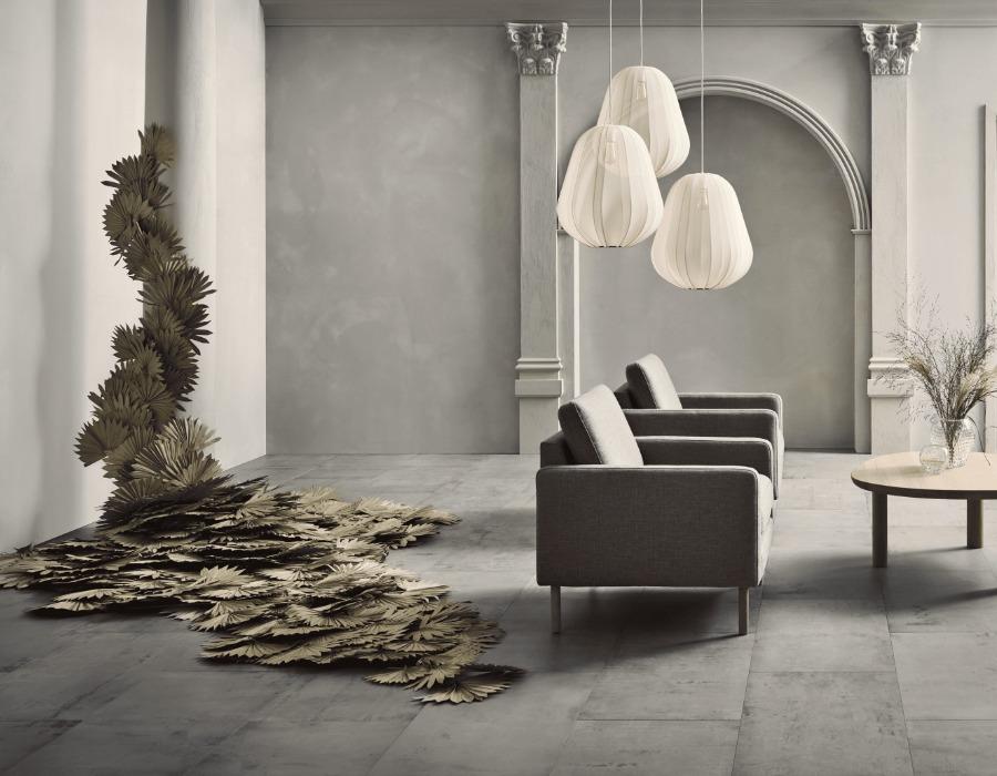 lampes blanches suspendus à coté de fauteuils et structure artistique qui longe le mur jusqu'au sol